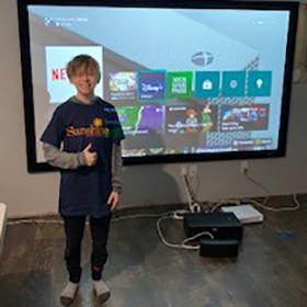 Carter stands in front of projector showing his gaming system