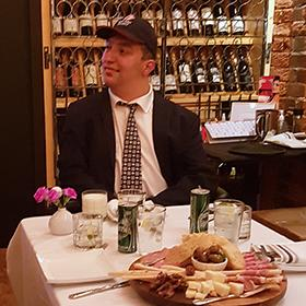Luke wears ball cap and suit, seated at a table with charcuterie board appetizer in a rustic restaurant