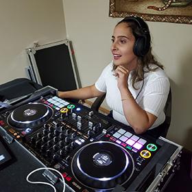 Razan sits behind her new DJ turn tables, wearing ear phone