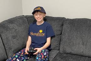 Carter sits in grey couch with video game controller